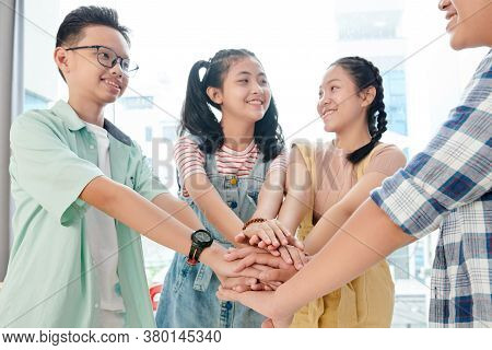 Vietnamese Smiling Teenage School Students Stacking Hands To Support Each Other Before Starting Work