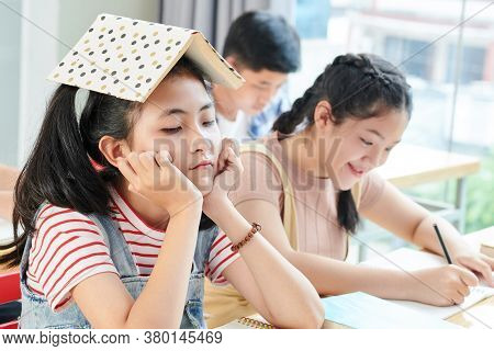 Bored Teenage Girl Sitting At School Desk With Opened Book On Her Head While Her Smiling Classmate W