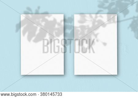 2 Vertical Sheets Of Textured White Paper On Soft Blue Table Background. Mockup Overlay With The Pla