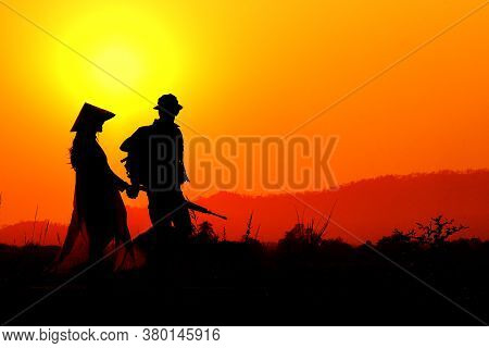Silhouette Of A Soldier Meeting In Love With A Vietnamese Woman In The Sunset.