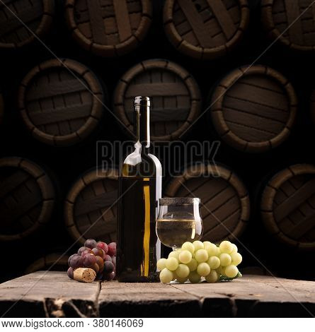 Bottle Of White Wine With Grapes On A Rustic Table In The Wine Cellar, Concept For Viticulture, Wine