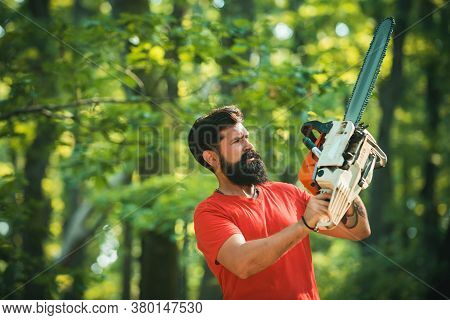 Lumberjack On Serious Face Carries Chainsaw. Harvest Of Timber. Lumberjack Worker Standing In The Fo