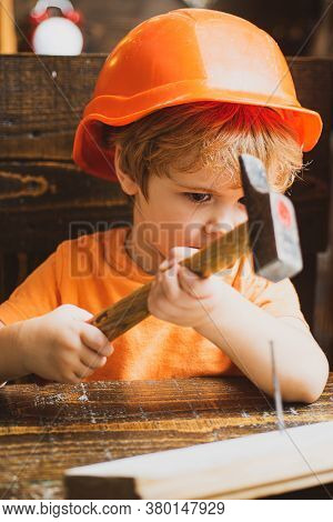 Cute Little Boy In Hard Hat Holding Wooden Plank And Hammer.