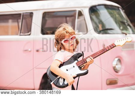 Kid Musician Playing The Guitar Like A Rockstar On Pink Background In Neon Light. Cute Pupil Having