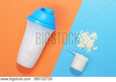 Protein Shake And Measuring Spoon With Powdered Protein On Blue And Orange Background, A Copy Of The