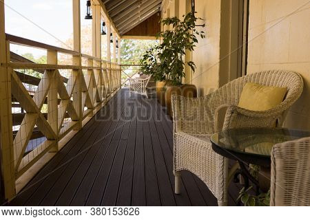 Cane Chairs And Table On Timber Verandah Of Queenslander Style House, Australia
