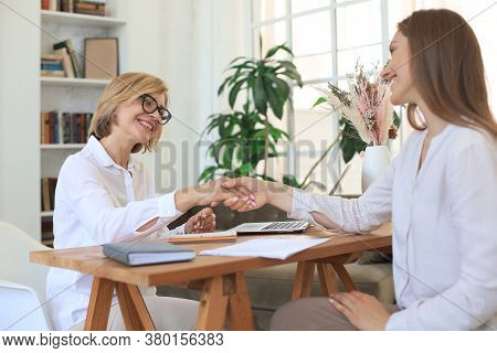 Cheerful Female Doctor Psychologist Shaking Grateful Patient Hands After Having A Consultation Meeti