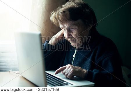 An old russian woman using laptop at home.