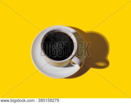 Hot Strong Black Coffee In White Elegant Cup With Saucer Over A Bright Yellow Background. Hot Mornin