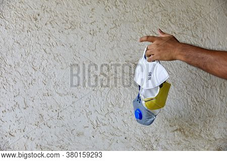 Adult Hands Holding Up Three Various Colorful Masks In Natural Light Against A Beige Textured Beige