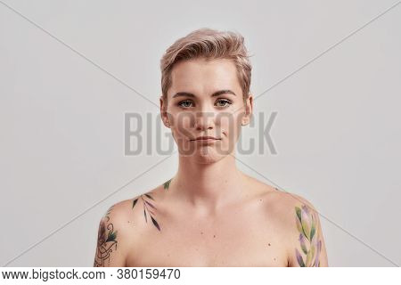 Portrait Of A Young Attractive Half Naked Tattooed Woman With Short Hair Looking With Smirk At Camer