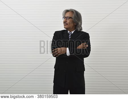Confident Elderly Asian Businessman In Black Suit And Eyeglasses Posing With Arms Crossed Standing O