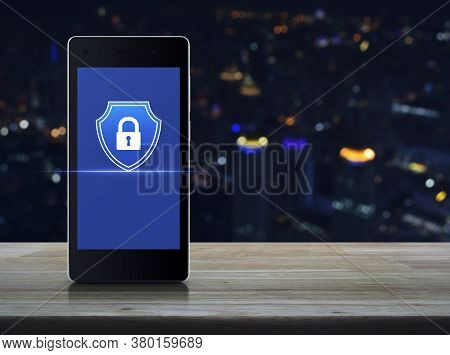 Padlock With Shield Flat Icon On Modern Smart Mobile Phone Screen On Wooden Table Over Blur Colorful