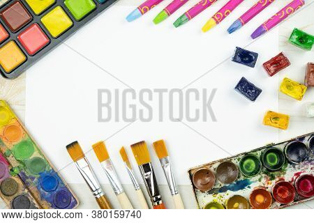 Flat Lay Painting Background With White Paper Sheet, Palette Of Watercolor Paints, Brushes, Colorful