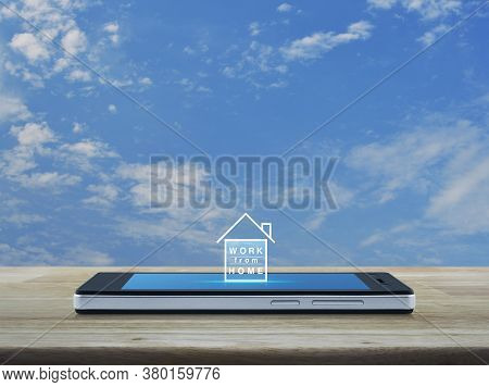 Work From Home Flat Icon On Modern Smart Mobile Phone Screen On Wooden Table Over Blue Sky With Whit