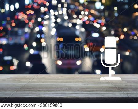 Microphone Flat Icon On Wooden Table Over Blur Of Colorful Night Light Rush Hour With Cars And Road
