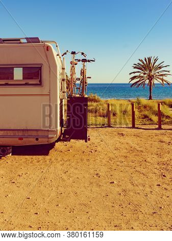 Camper, Recreational Vehicle With Bicycles Camping On Beach, Mediterranean Coast With Palm Trees In