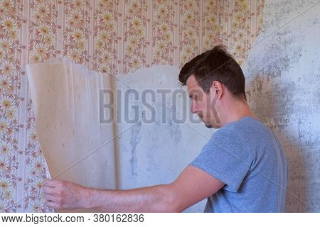 Man Is Making Renovation Removing Wallpapers From Wall Using Spatula. Construction Works In Room In