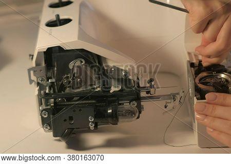 Seamstress Woman Is Repairing Sewing Machine In Workshop, Closeup Hands View. Maintenance And Repair