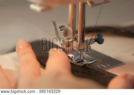 Seamstress Is Working Sewing Clothes In Sewing Machine, Hands Closeup. Process Of Sewing In Atelier