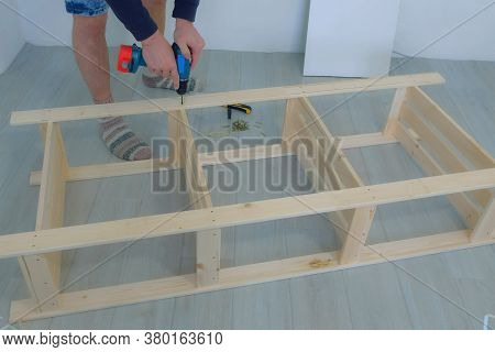 Man Screwing Boards With Bolts Using Electric Screwdriver Collecting Rack Furniture Bookcase, Hands