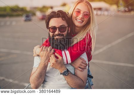 Cheerful Blond Female Smiling And Embracing Bearded Boyfriend While Having Fun On Parking Lot Togeth