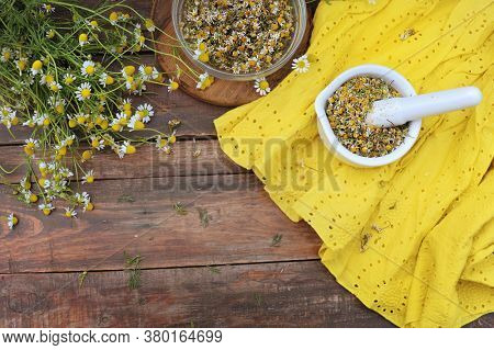Organic chamomile flowers in porcelain pestle standing on a wooden table, nature treatment concept, top view
