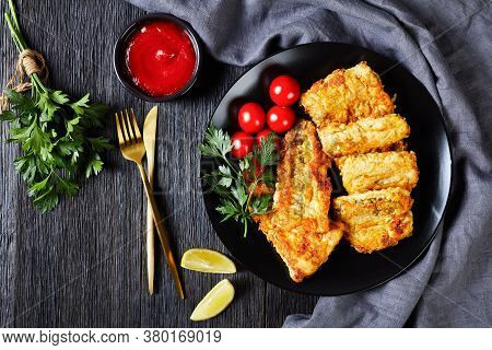 Crispy Fried Hake Fish Fillet Served On Black Plate With Lemon Wedges, Cherry Tomatoes, Ketchup, Fre