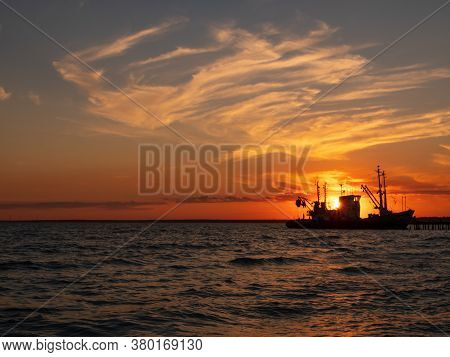 Beautiful Orange Sunset On Sea Water. Transport Ship On The Dock In The Evening On Seacoast. Shippin