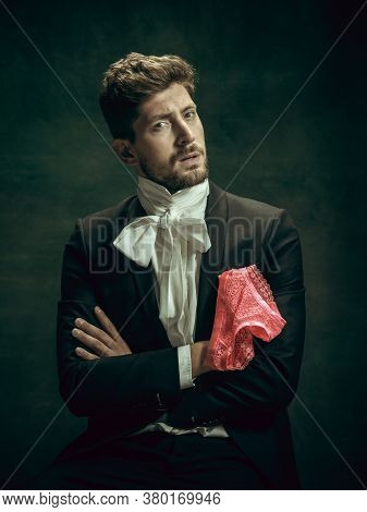 Passioned. Young Man In Suit As Dorian Gray Isolated On Dark Green Background. Retro Style, Comparis