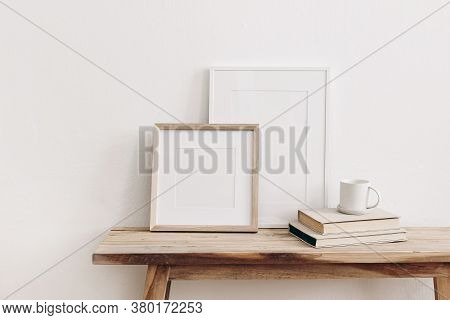 Wooden Square And White Portrait Frame Mockups On Vintage Bench, Table. Cup Of Coffee On Pile Of Boo