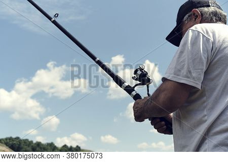 Man Fisherman Catches A Fish.fishing, Spinning Reel, Fish. The Concept Of A Rural Getaway.