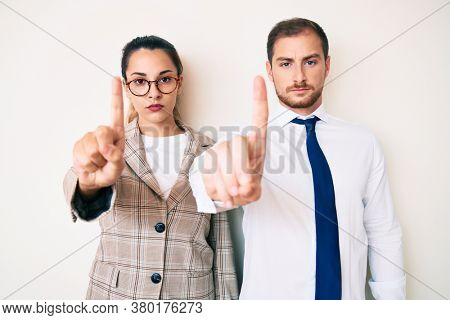 Beautiful couple wearing business clothes pointing with finger up and angry expression, showing no gesture