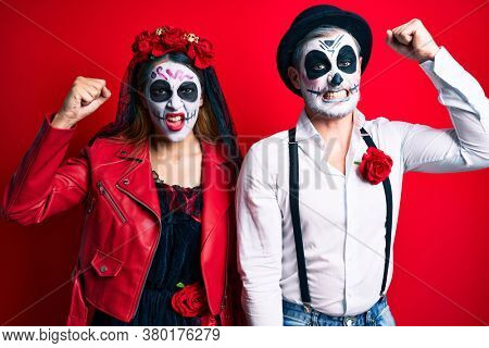 Couple wearing day of the dead costume over red angry and mad raising fist frustrated and furious while shouting with anger. rage and aggressive concept.