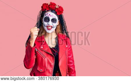 Woman wearing day of the dead costume over background angry and mad raising fist frustrated and furious while shouting with anger. rage and aggressive concept.