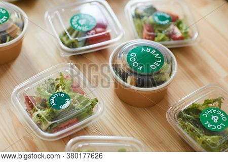 Above View Background Of Healthy Food Portions In Plastic Packaging On Wooden Table In Food Delivery