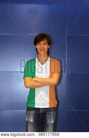 Man Wearing Ireland Flag Pattern Shirt And Cross One's Arm On The Blue Wall Background, A Vertical T