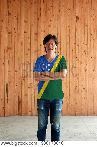 Man Wearing Solomon Islands Flag Color Shirt And Cross One's Arm On Wooden Wall Background, A Thin Y