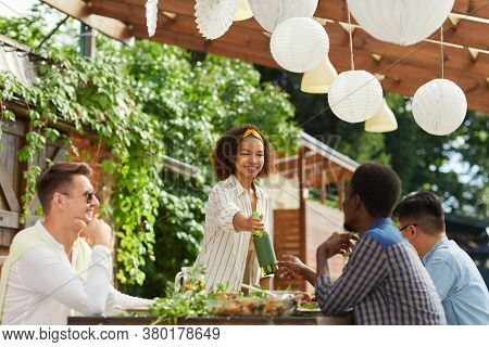 Multi-ethnic Group Of People Enjoying Dinner At Outdoor Terrace In Summer, Focus On Smiling African-