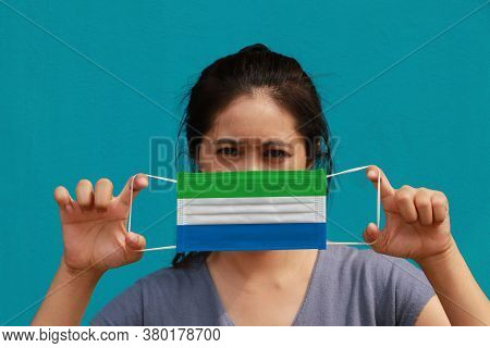 A Woman With Sierra Leone Flag On Hygienic Mask In Her Hand And Lifted Up The Front Face On Light Bl