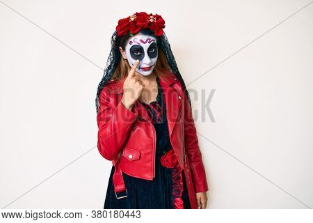 Woman wearing day of the dead costume over white pointing to the eye watching you gesture, suspicious expression