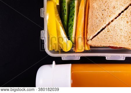 Bread Sandwich And Vegetables In A Lunch Box Next To A Bottle Of Juice - Top View And Copy Space. He