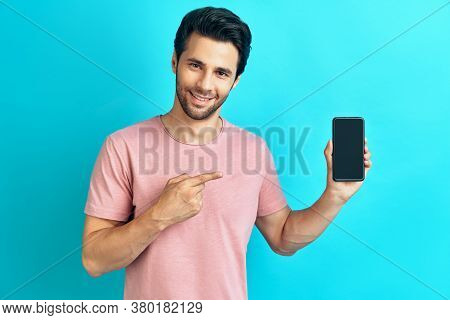 Portrait Of Smiling Man Pointing To Mobile Phone. Young Handsome Male Showing Smartphone Blank Scree