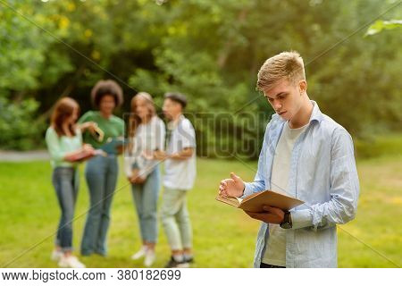 College Bullying. Lonely Student Guy Standing With Book At Campus Apart From Classmates, Reading, Pr