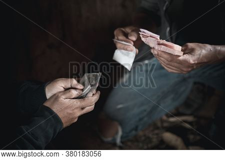 Dealer Is Holding Drug Bag And Money In His Hand On A Black Background. Drug Trafficking, Crime, Add