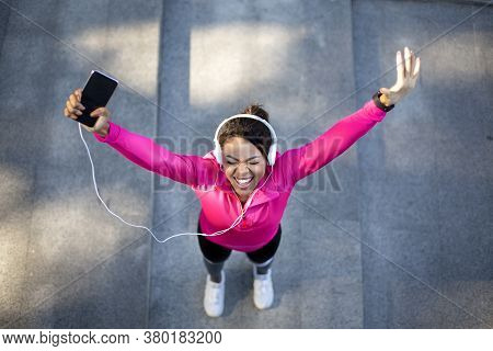 Top View Of Emotional Female Black Jogger With Headset Holding Smartphone, Raising Hands Up, Enjoyin