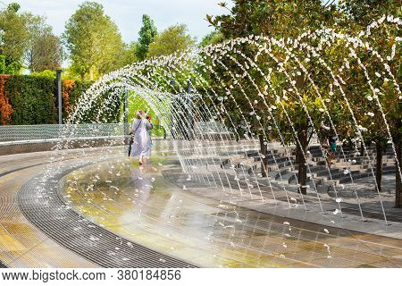 Beautiful Fountain In Krasnodar. You Can Pass Under The Arc Of Water. A Splash Cascade Forms A Passa