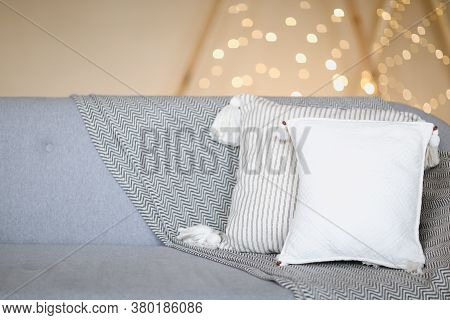 Gray Soft Couch With White Pillows Against Blurred Brown Wall With Lights As Symbol Of Warmth And Co
