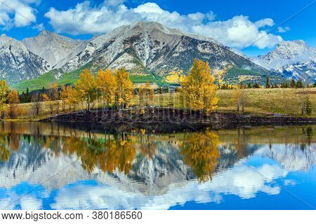 Bright autumn forest is reflected in the lake. Three Sisters Mountain in Canadian Banff Park. Outskirts of Kenmore. The concept of active, ecological and photo tourism