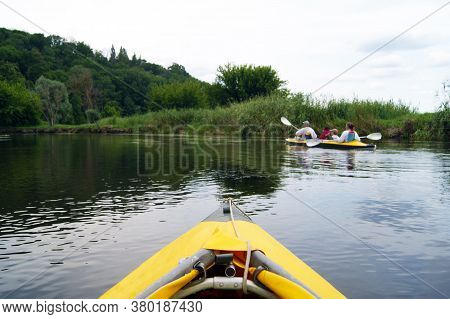 Family Rowing In A Yellow Kayak In Summer Along The Trees At The Bank Of Seversky Donets River.